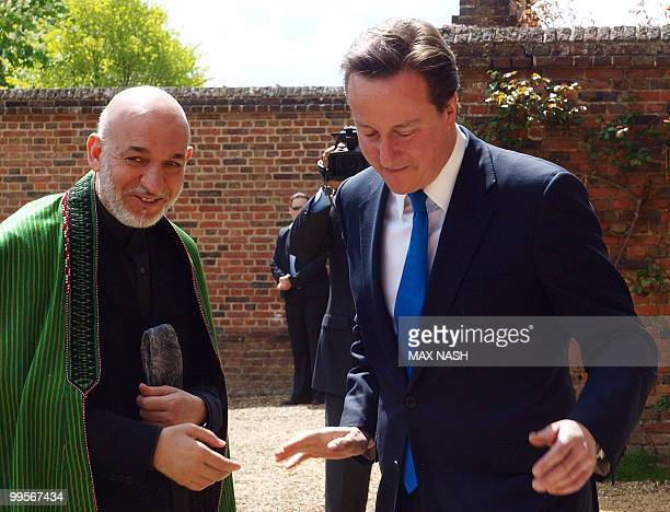 Britain's Prime Minister David Cameron greets Afganistan's President Hamid Karzai oh his arrival at the Prime Minister's country residence of...