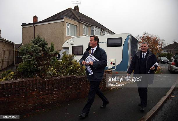 Britain's Prime Minister David Cameron helps Ken Maddock Avon and Somerset Police and Crime Commissioner candidate for the Conservative party deliver...
