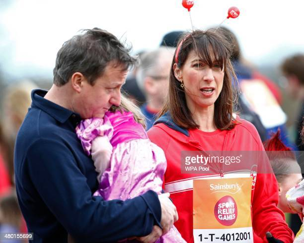 Britain's Prime Minister David Cameron holds his daughter Florence before taking part in the Sport Relief Mile run for charity with his wife Samantha...