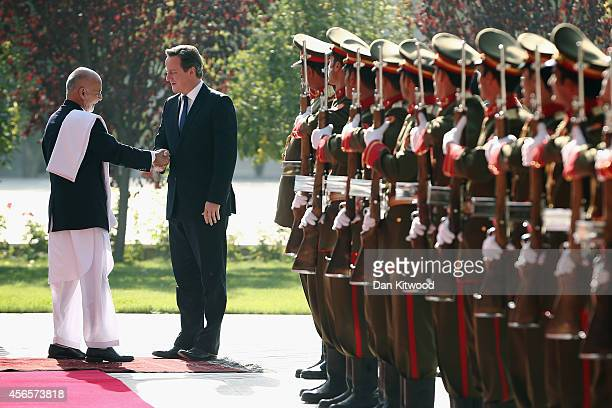 Britain's Prime Minister David Cameron is welcomed to the Presidential Palace by Afghanistan's President Ashraf Ghani on October 3 2014 in Kabul...