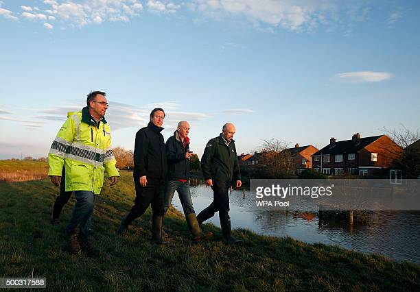 Britain's Prime Minister David Cameron looks at the flood defence system on Warwick Road during a visit to flood hit areas on December 7 2015 in...
