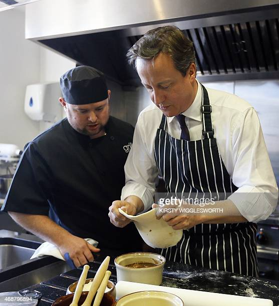 Britain's Prime Minister David Cameron makes a steak ale and stilton pie during a visit to Brains Brewery in Cardiff Wales on April 7 2015 while on...