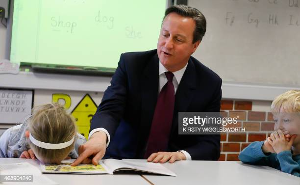 Britain's Prime Minister David Cameron reads a book to Lucy Howarth and Joshua Davies during a visit to Sacred Heart RC primary school in...