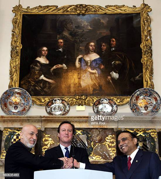 Britain's Prime Minister David Cameron shakes hands with Afghan President Hamid Karzai and Pakistani President Asif Ali Zardari at the Prime...