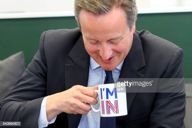 Britain's Prime Minister David Cameron sips from an I'm In mug as he meets television presenters Jeremy Clarkson and James May during a visit to W...