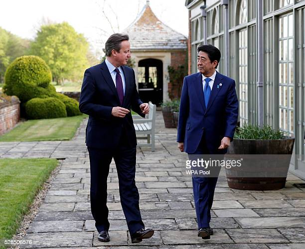 Britain's Prime Minister David Cameron speaks with Japan's Prime Minister Shinzo Abe as they walk in the gardens at Chequers the Prime Minister's...