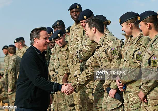 Britain's Prime Minister David Cameron talks to British soldiers during a visit to Camp Bastion on December 16 2013 near Lashkar Gah the provincial...