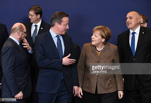 Britain's Prime Minister David Cameron talks with German Chancellor Angela Merkel as they lineup for the Family photo at the European Summit in...