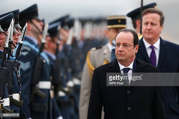 Britain's Prime Minister David Cameron walks behind as France's President Francois Hollande as he reviews an honour guard at RAF Brize Norton on...