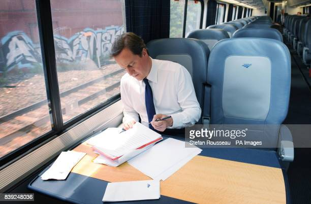 Britain's Prime Minister David Cameron works onboard the Acela Express from Wasington DC Washington to New York's Penn Station as part of his two day...