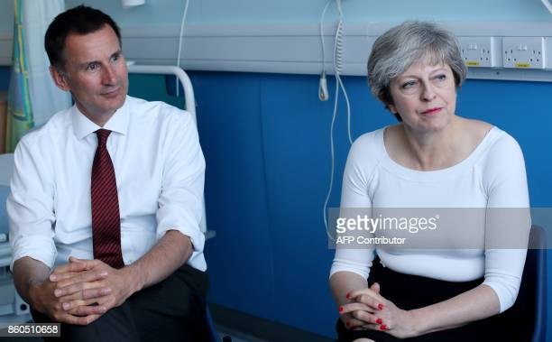 Britain's Prime Minister Theresa May and Britain's Health Secretary Jeremy Hunt talk with patients during a round table discussion during their visit...