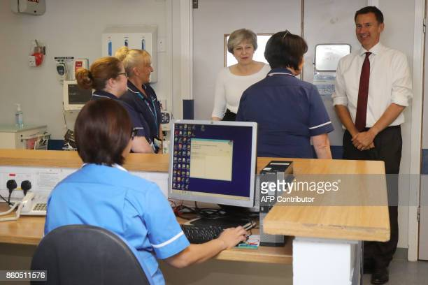Britain's Prime Minister Theresa May and Britain's Health Secretary Jeremy Hunt meet nursing staff during their visit to the Renal Transplant Unit at...