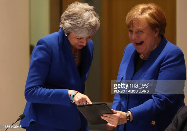 TOPSHOT Britain's Prime minister Theresa May and Germany's Chancellor Angela Merkel look at a tablet ahead of a European Council meeting on Brexit at...