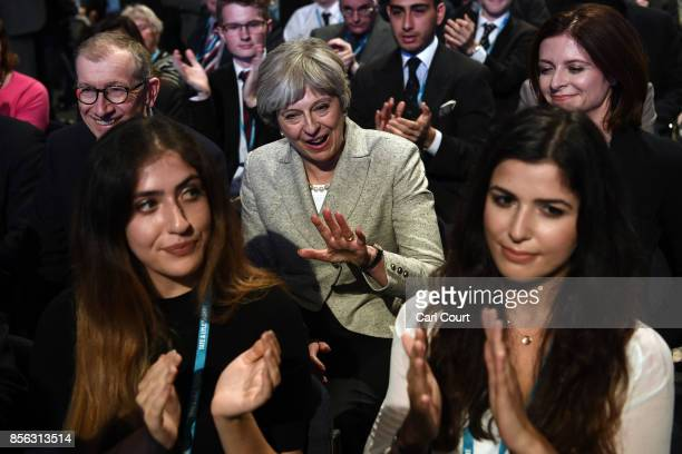 Britain's Prime Minister Theresa May and her husband Philip applaud a speaker on the first day of the annual Conservative Party conference on October...