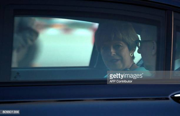 Britain´s Prime Minister Theresa May and her husband Philip John sit it the car after arriving at the airport in Hamburg northern Germany on July 6...