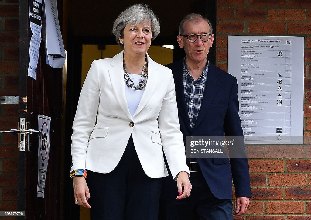Britain's Prime Minister Theresa May and her husband Philip, leave a Polling Station after casting their ballot paper in Sonning, west of London, on June 8, 2017, as Britain holds a general election. As polling stations across Britain open on Thursday, opinion polls show the outcome of the general election could be a lot tighter than had been predicted when Prime Minister Theresa May announced the vote six weeks ago. / AFP PHOTO / Ben STANSALL