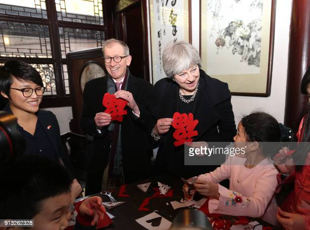 Britain's Prime Minister Theresa May and her husband Philip May watch students doing papercut as they visit Yu Garden in Shanghai on February 2 2018...