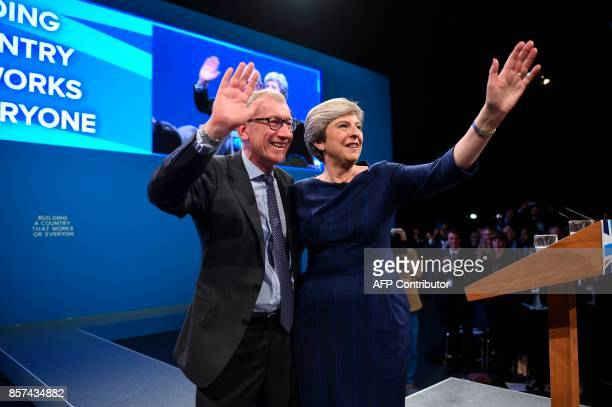 Britain's Prime Minister Theresa May and her husband Philip May wave from the stage at the end of her speech on the final day of the Conservative...
