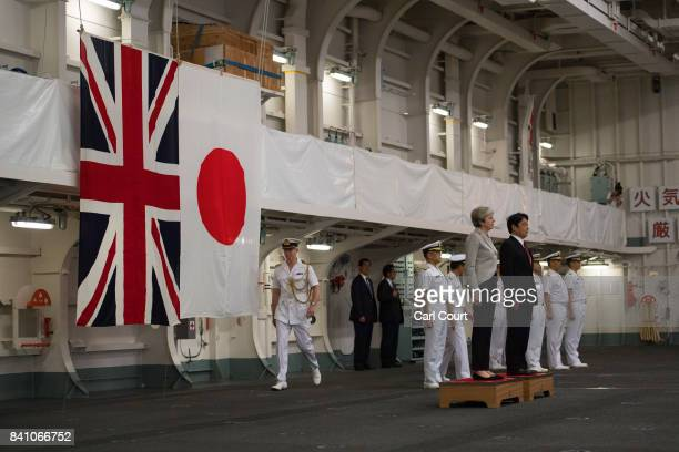Britain's Prime Minister Theresa May and Japan's Defence Minister Itsunori Onodera listen to the two countries national anthems on board the Japanese...
