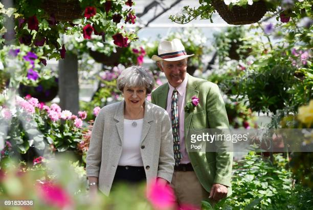 Britain's Prime Minister Theresa May and nursery owner Tom Horsfield walk during an election campaign visit to Horsfields Nursery on June 3 2017 in...