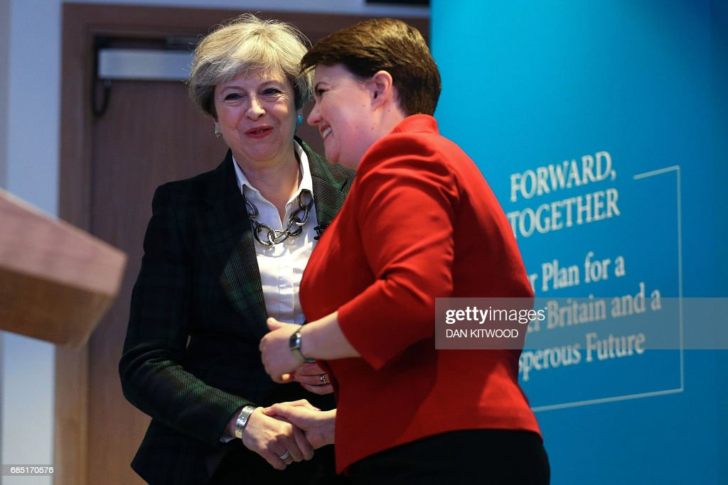 Britain's Prime Minister Theresa May (L) and Scottish Conservative leader Ruth Davidson shake hands at the launch of the Scottish manifesto in Edinburgh on May 19, 2017. / AFP PHOTO / POOL / Dan Kitwood
