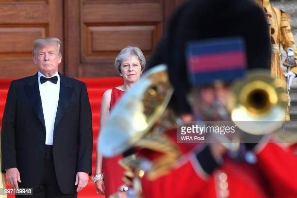 Britain's Prime Minister Theresa May and US President Donald Trump look on as a military band plays at Blenheim Palace on July 12 2018 in Woodstock...