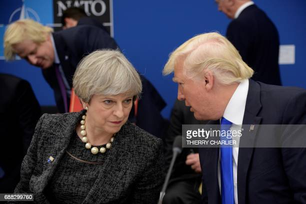 Britain's Prime Minister Theresa May and US President Donald Trump speak together during the NATO summit at the NATO headquarters in Brussels on May...
