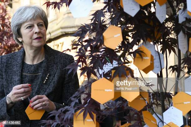 Britain's Prime Minister Theresa May attaches her own personal message of support to a 'tree of hope' a memorial set up for the Manchester Arena...