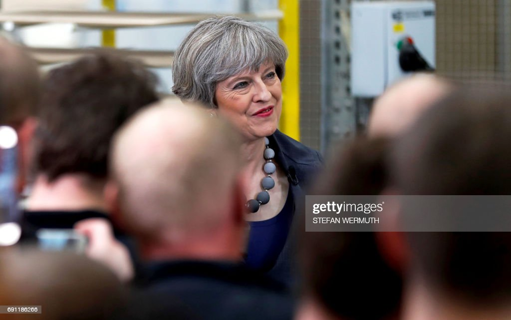 Britain's Prime Minister Theresa May attends a 'question and answer' session with staff at Ultima Furniture in Pontefract, west Yorkshire on June 1, 2017, as she campaigns in the run-up to the June 8 general election. /