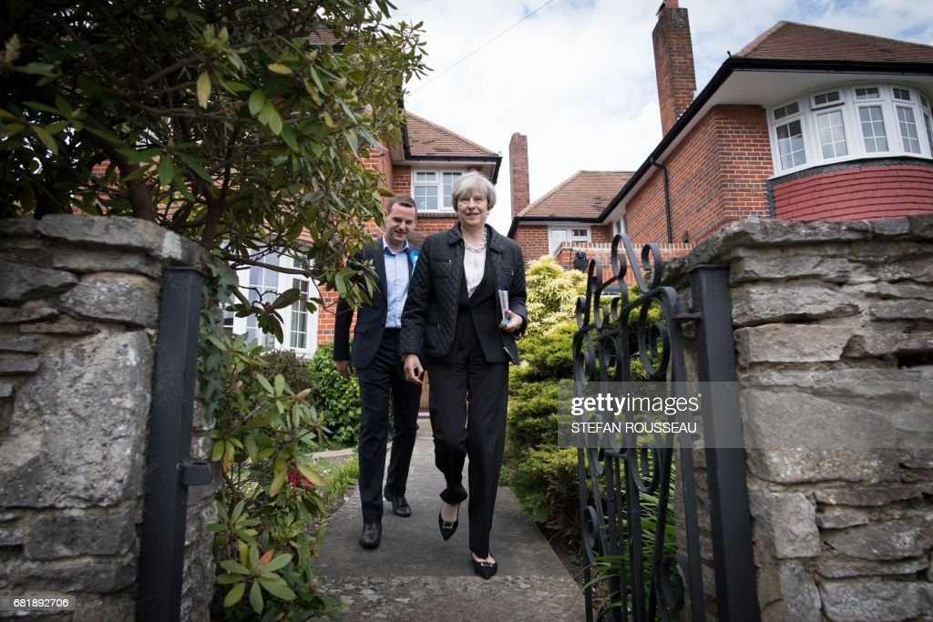 Britain's Prime Minister Theresa May campaigns with Conservative candidate for the Southampton Test constituency, Paul Holmes (L), during a general election campaign visit in Southampton, southern England on May 11, 2017. Britain will vote in a general election on June 8. / AFP PHOTO / POOL / Stefan Rousseau