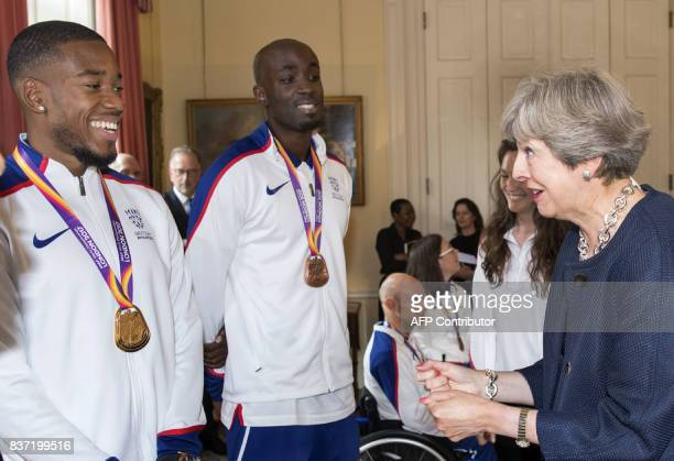 Britain's Prime Minister Theresa May chats to 4x100 m relay athlete Nethaneel MitchellBlake and 4x400m relay athlete Wayne Cowan during a reception...