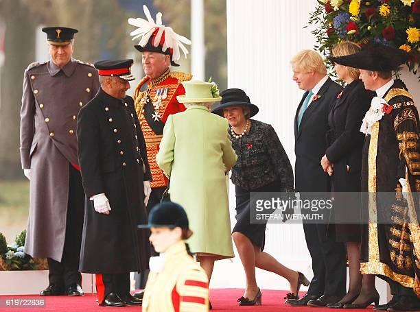Britain's Prime Minister Theresa May curtseys as she greets Britain's Queen Elizabeth II by British Foreign Secretary Boris Johnson and Home...