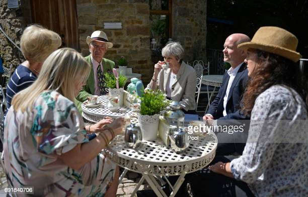 Britain's Prime Minister Theresa May drinks tea during an election campaign visit to Horsfields Nursery on June 3 2017 in Silkstone South Yorkshire...
