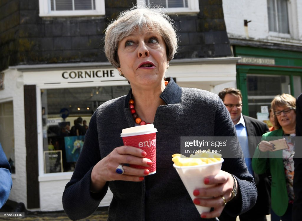 Britain's Prime Minister Theresa May eats chips as she meets with residents in Mevagissey, south-west England, on May 2, 2017, during a campaign visit ahead of the forthcoming elections. - Victory in the places that swing between May's Conservatives and the opposition Labour party could prove crucial in gaining momentum ahead of the June 8 general elections.