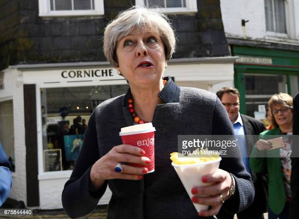 Britain's Prime Minister Theresa May eats chips as she meets with residents in Mevagissey, south-west England, on May 2 during a campaign visit ahead...
