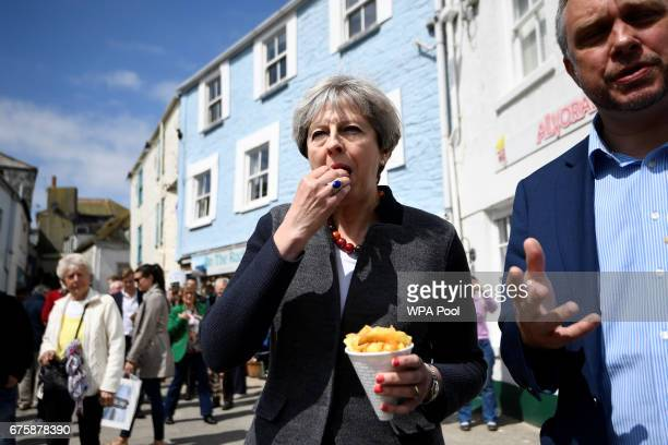Britain's Prime Minister Theresa May enjoys some chips during a campaign stop on May 2 2017 in Mevagissey Cornwall England The Prime Minister is...