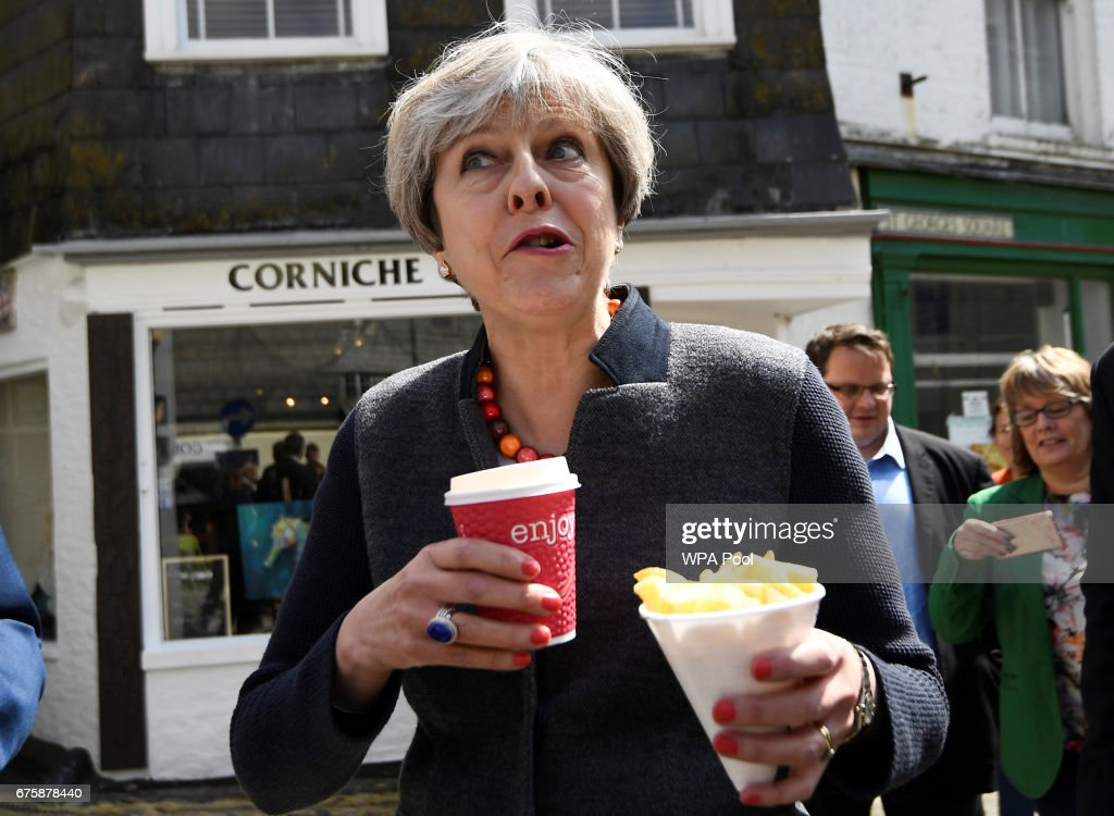 Britain's Prime Minister Theresa May enjoys some chips during a campaign stop on May 2, 2017 in Mevagissey, Cornwall, England. The Prime Minister is campaigning in South-West England, a former Liberal Democrat stronghold, as she urges West Country voters to stick with her party ahead of the polls on June 8.