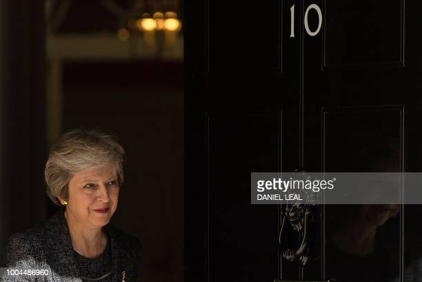 TOPSHOT Britain's Prime Minister Theresa May exits 10 Downing Street to greet the Emir of Qatar Sheikh Tamim Bin Hamad alThani in London on July 24...