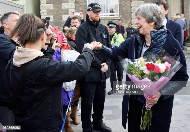 Britain's Prime Minister Theresa May 'fistbumps' a member of the public during her visit to Salisbury southern England on March 15 where she visited...