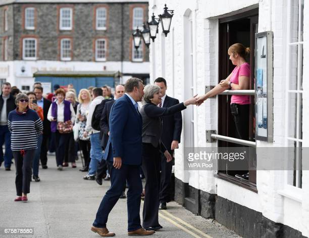 Britain's Prime Minister Theresa May greets a woman during a campaign stop on May 2 2017 in Mevagissey Cornwall England The Prime Minister is...