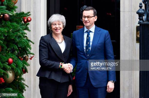 Britain's Prime Minister Theresa May greets Poland's Prime Minister Mateusz Morawiecki outside of 10 Downing Street in central London on December 20...