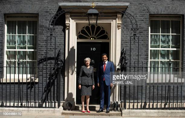 Britain's Prime Minister Theresa May greets the Emir of Qatar Sheikh Tamim Bin Hamad alThani on the steps of 10 Downing Street in London on July 24...