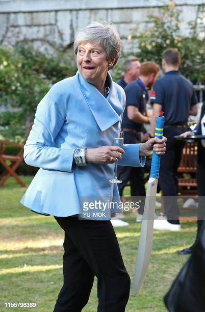 Britain's Prime Minister Theresa May holds a bat in the garden of 10 Downing Street at a reception in London on July 15 a day after they won the 2019...