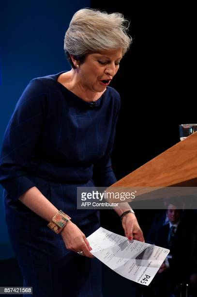 Britain's Prime Minister Theresa May holds a piece of paper written as a mock P45 that was given to her by a protester comedian Simon Brodkin whilst...