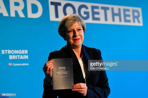 Britain's Prime Minister Theresa May holds up the Conservative Party general election manifesto as she speaks at the launch event in Halifax in...