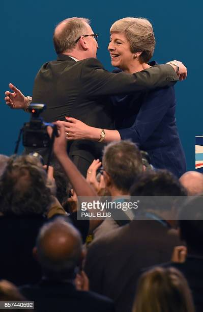 Britain's Prime Minister Theresa May is embraced by her husband Philip May after delivering her speech on the final day of the Conservative Party...