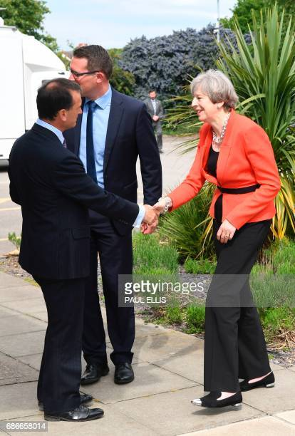 Britain's Prime Minister Theresa May is greeted by Conservative candidate for Wrexham Andrew Atkinson and Britain's Wales Secretary Alun Cairns as...