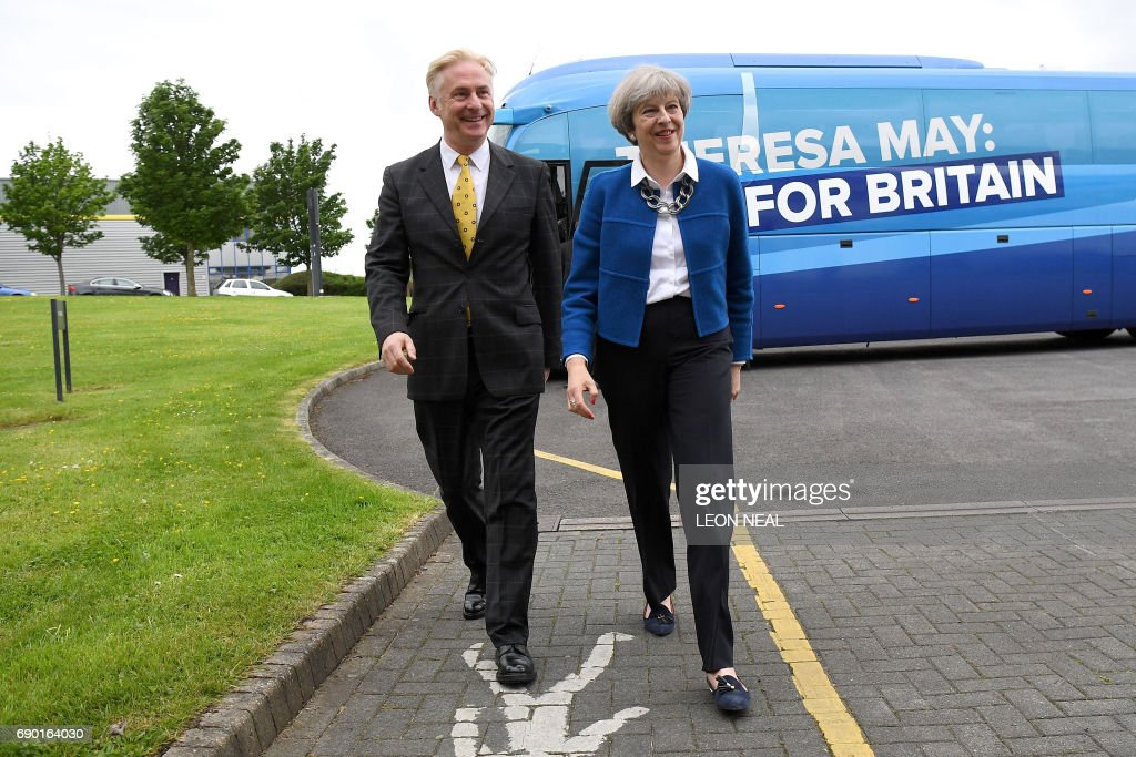 Britain's Prime Minister Theresa May (R) is greeted by local Conservative candidate, Kevin Horkin as she arrives in the constituency of Hyndburn in Accrington, Lancashire county on May 30, 2017. / AFP PHOTO / POOL / Leon Neal