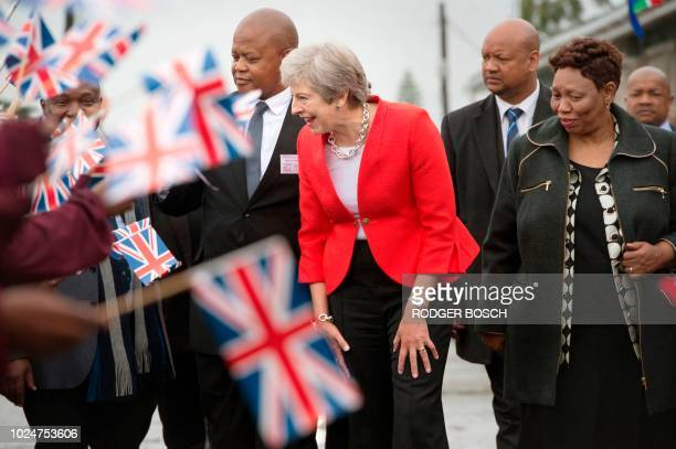 Britain's Prime Minister Theresa May is greeted by schoolchildren waving British and South African flags, during a visit to the ID Mkhize Secondary...
