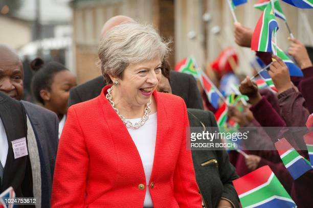 Britain's Prime Minister Theresa May is greeted by schoolchildren waving British and South African flags during a visit to the ID Mkhize Secondary...